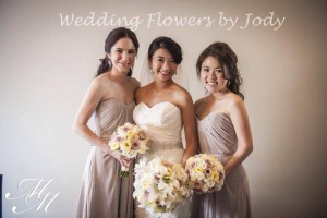 A gorgeous bride with two bridesmaids in bronze coloured dresses.