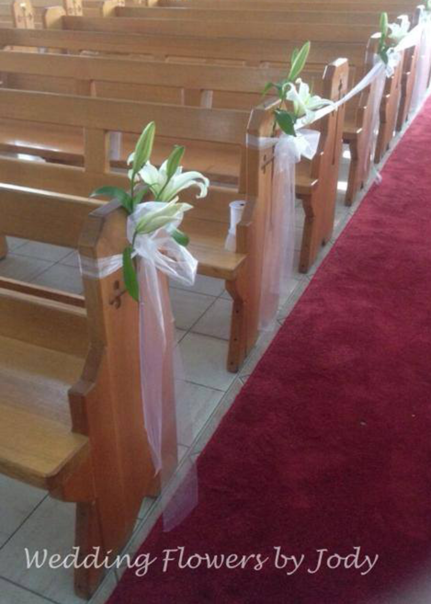 Oriental lillies decorating church pew ends